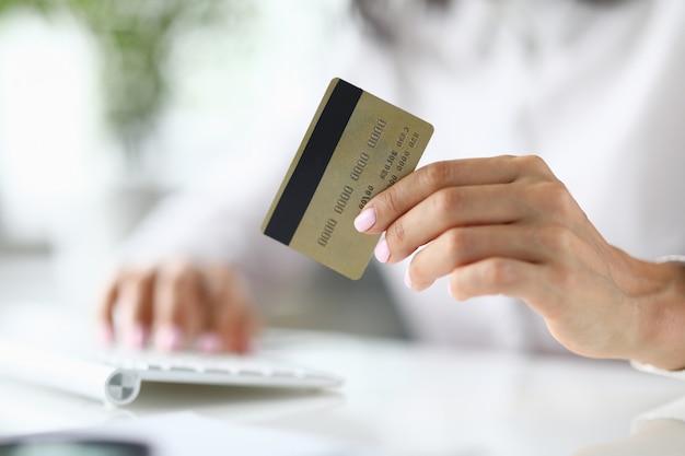 女性の手を保持する銀行のプラスチックカードのクローズアップ