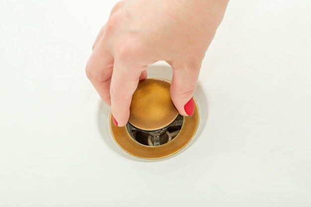Female hand holds bathtub drain plug