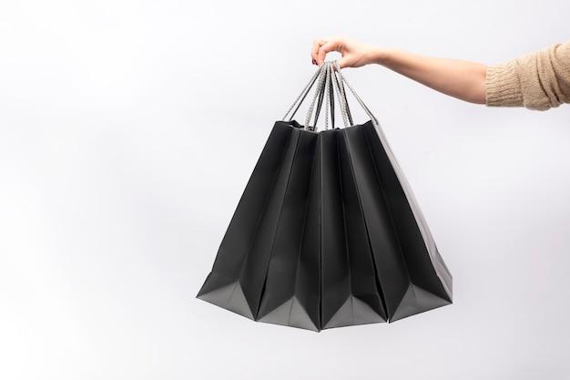 女性の手は白い背景で隔離の黒い紙の買い物袋を保持します。