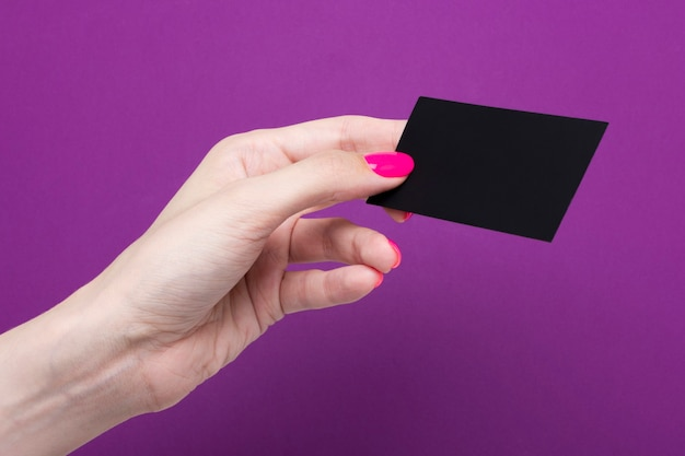 Female hand holds a blank business card on a purple background.