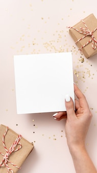 Female hand holds blank square paper mockup, golden stars confetti, gift boxes on beige background. flat lay, top view, copy space, minimalist. christmas and new year concept