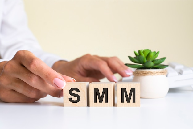 Female hand holds a block with the letter s from the word smm. the word is located on a white office table on the background of a white keyboard. financial, marketing and business concepts