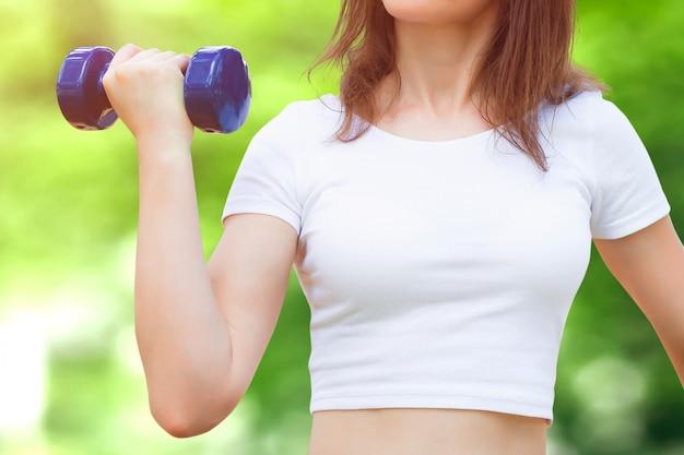 Female hand holds a blue dumbbell