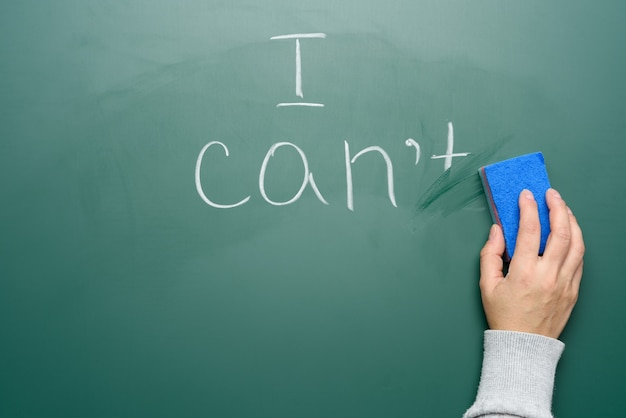 Female hand holds a blue sponge for wiping off the chalk green board and wipes part of the phrase, motivation and self-confidence