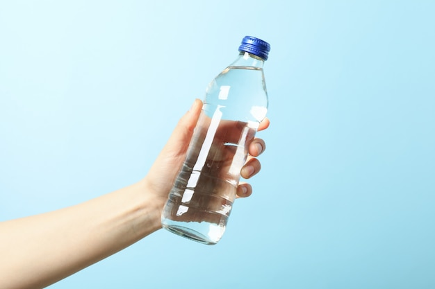 Female hand holds bottle with water on blue, close up