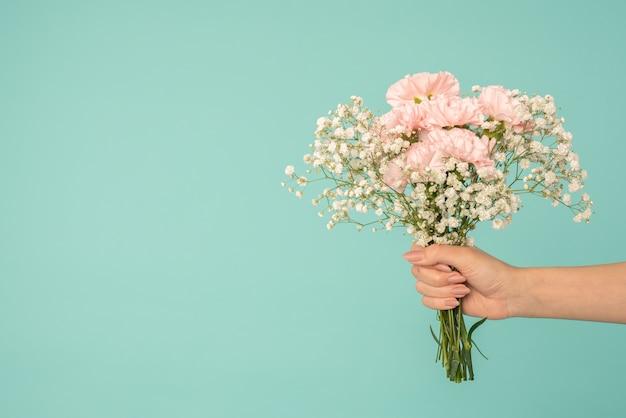 女性の手は、コピースペースで青い背景の上に分離された白とピンクの花の花束を保持します。