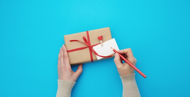 Female hand holds a box wrapped in brown kraft paper and tied with a silk red ribbon