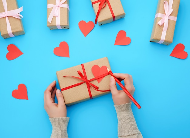 Female hand holds a box wrapped in brown kraft paper and tied with a silk ribbon on a blue background