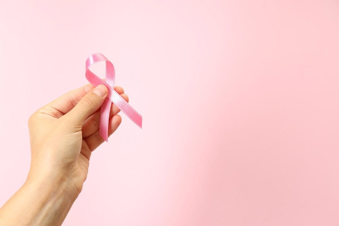 Female hand holds breast cancer awareness ribbon on pink background
