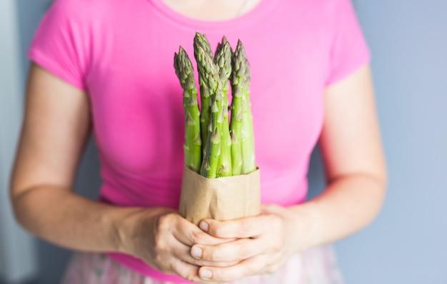 女性の手はビーガン菜食主義者と健康食品のグリーンアスパラガスの概念の束を保持します