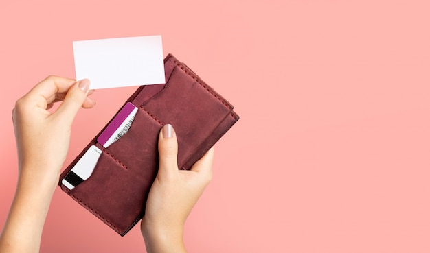 Female hand holds a burgundy leather purse with credit cards and takes out a blank business card on a pink background with copy space. branding mockup template.