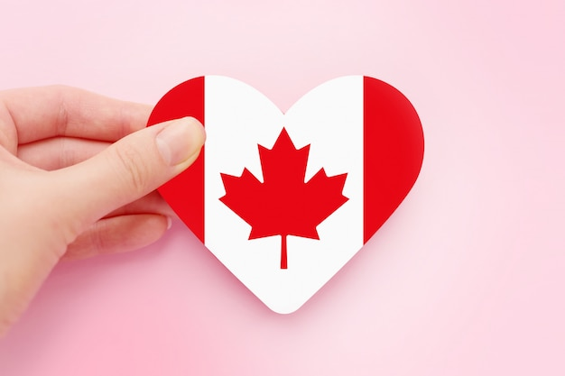 Female hand holds canada heart shaped paper flag isolated over pink space, canada day