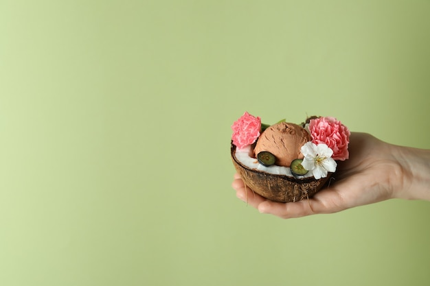 Female hand holds coconut with fruit ice cream on green background