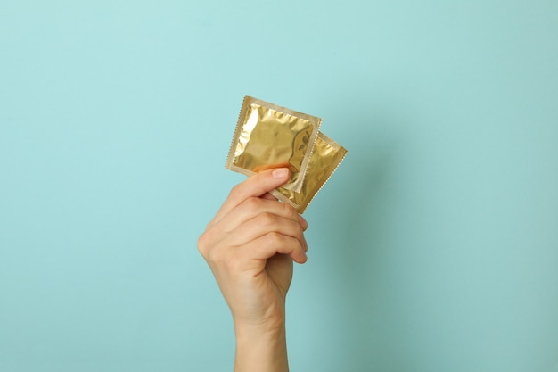 Female hand holds condoms on blue surface