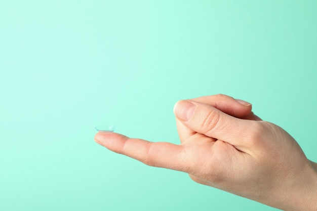 Female hand holds contact lens on mint surface, space for text