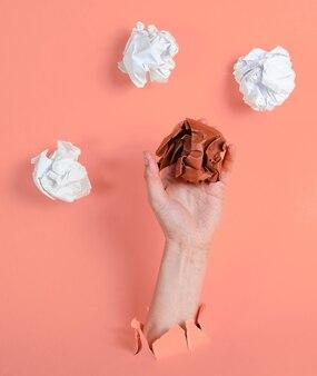 女性の手は、引き裂かれた黄色い紙を通して紙のしわくちゃのボールを保持します。ミニマルなアイデアのビジネスコンセプト