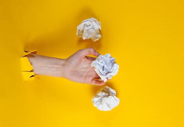 女性の手は、引き裂かれた黄色い紙を通して紙のしわくちゃのボールを保持しています。ミニマルなアイデアビジネスコンセプト