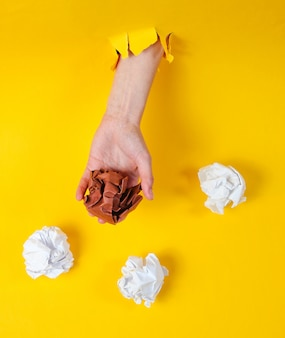 Female hand holds crumpled balls of paper through torn yellow paper. minimalistic idea business concept