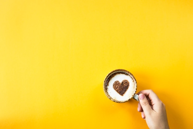 A female hand holds a cup of coffee on which a heart is drawn