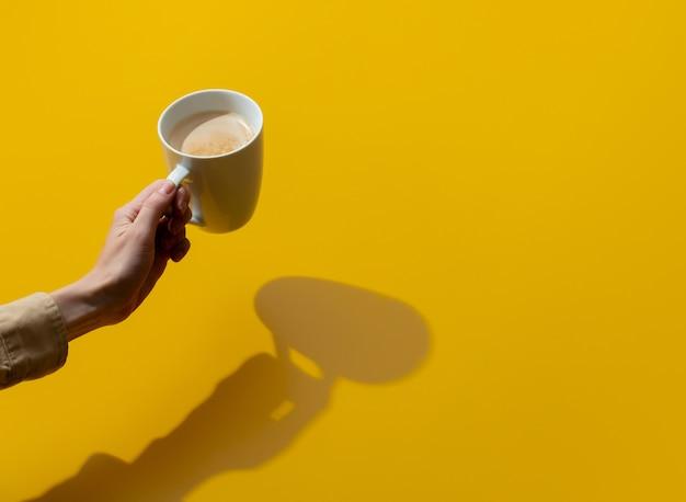 여성 손 노란색 표면에 커피 한잔 보유