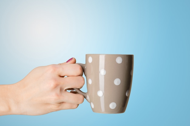 Female hand holds a cup of tea