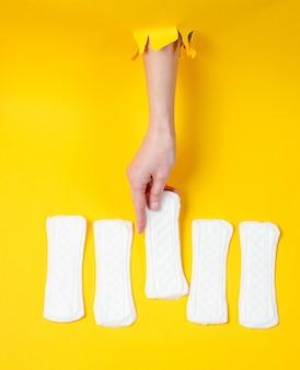 女性の手は、引き裂かれた黄色い紙の穴を通して毎日生理用ナプキンを保持しています。ミニマルなファッションのコンセプト