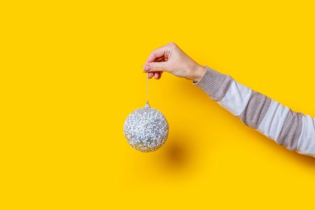여성 손은 노란색 배경에 장식용 크리스마스 공을 들고 있습니다.