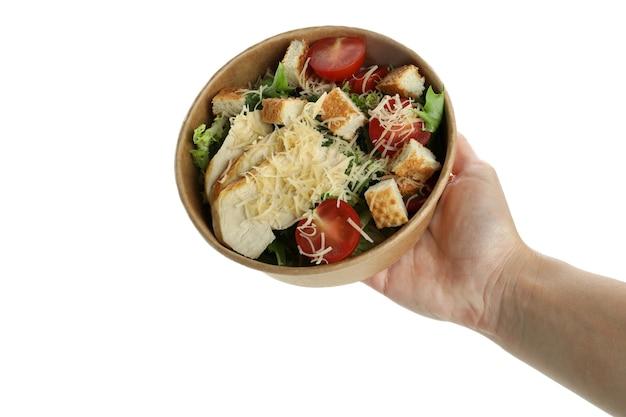 Женская рука держит миску с салатом цезарь, изолированную на белом фоне
