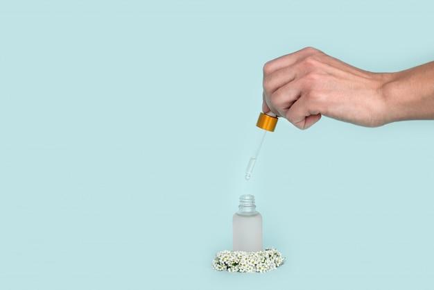 여성 손 보유 스포이드 유리 병 화장품 피 펫 기름. 모형. 청록색 배경에 작은 흰색 꽃을 가진 여성을위한 화장품 용기