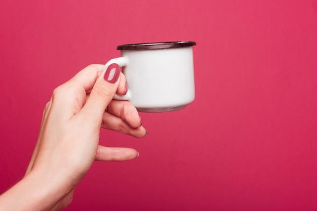 The female hand holds an enameled mug white with a black edge