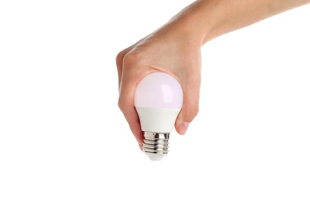 Женская рука держит энергосберегающую лампочку, изолированную на белом фоне.