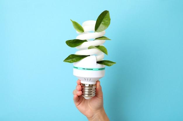 Женская рука держит энергосберегающую лампочку на синем фоне