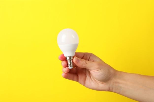 Женская рука держит энергосберегающую лампочку на желтом фоне.