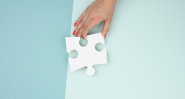 Female hand holds a fragment of a white large puzzle on a blue background, the concept of finding an idea, solving a problem