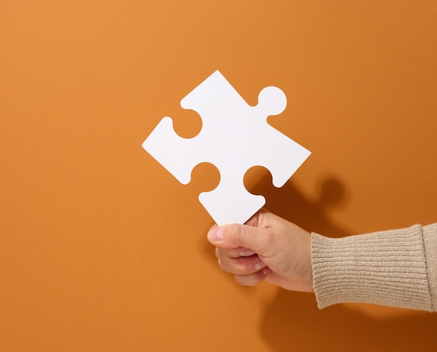 Female hand holds a fragment of a white large puzzle on a brown background, the concept of finding an idea, solving a problem
