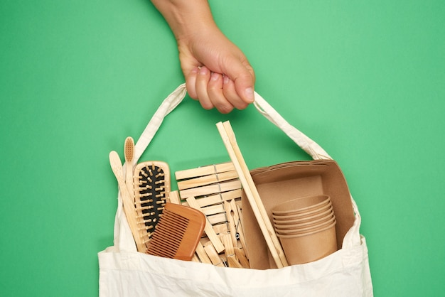 Female hand holds full textile bag of recyclable household items, green surface, zero waste