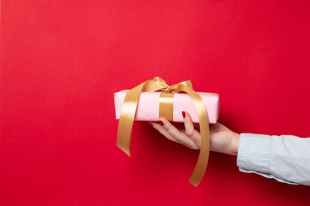 Female hand holds a gift wrap wrapped in pink paper and a gold ribbon bow on red