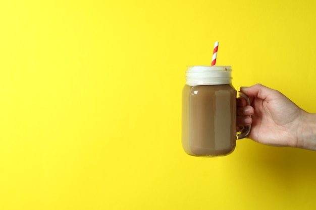 Female hand holds glass jar of ice coffee on yellow