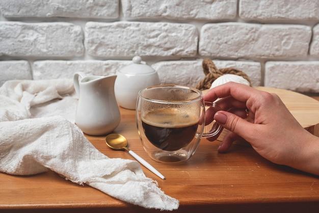 Female hand holds a glass mug with coffee