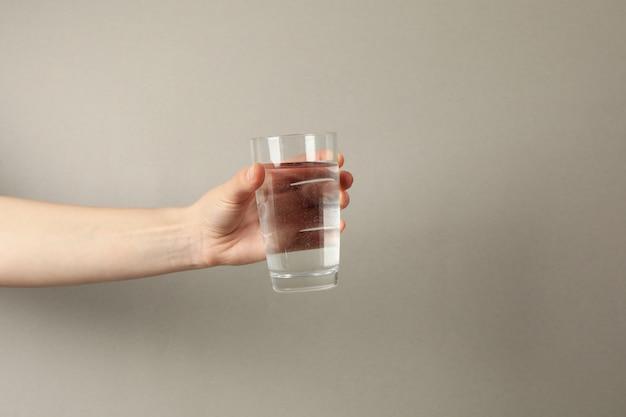 Женская рука держит стакан воды на сером, место для текста