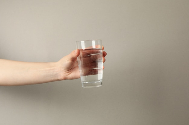Female hand holds glass of water on gray, space for text