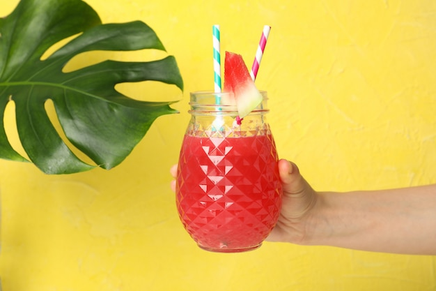 Female hand holds glass of watermelon juice on yellow space