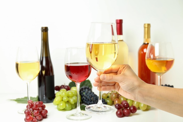 Female hand holds glass of white wine against various wines