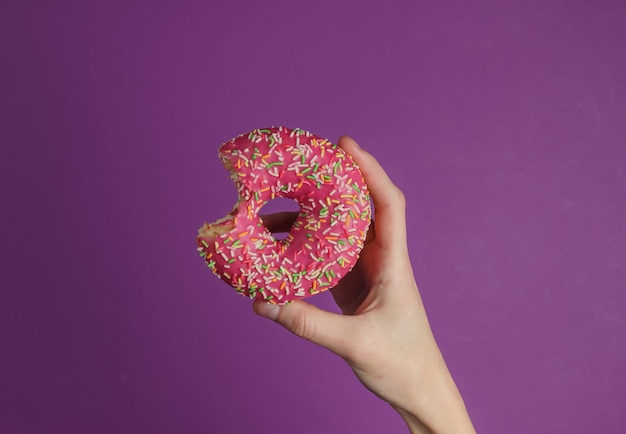 Female hand holds a glazed donut on purple background.  sweet dessert. top view.