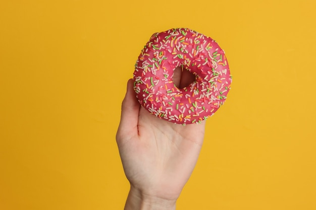 Female hand holds a glazed donut on yellow background.  sweet dessert. top view.