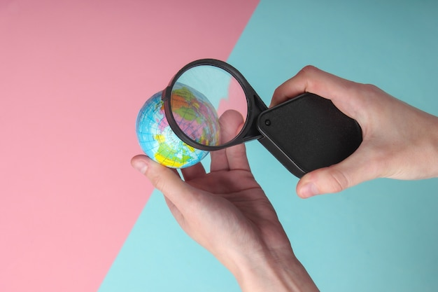 Female hand holds a globe with a magnifying glass on blue-pink pastel background. travel, tourism concept