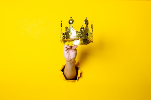 Female hand holds a gold crown on a bright yellow background