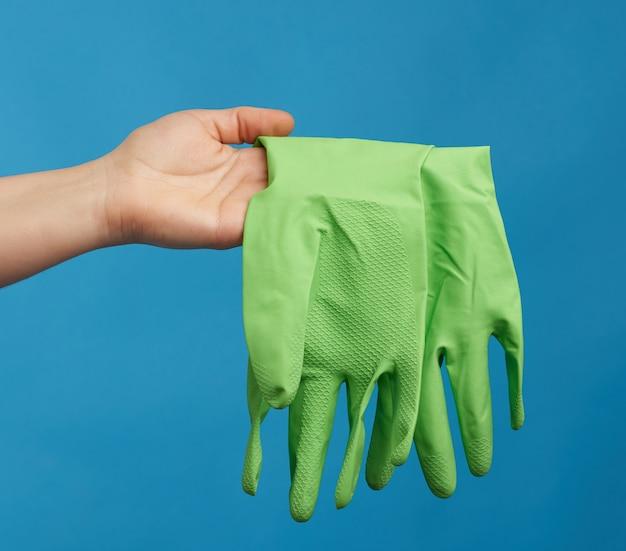 女性の手は、青い背景のクリーニングのための緑のゴム手袋を保持しています。