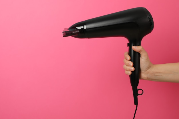 Female hand holds hairdryer, space for text