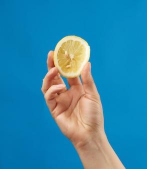 Женская рука держит половину желтого лимона и сжимает его